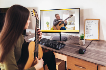 Focused girl playing acoustic guitar and watching online course on laptop while practicing at home. Online training, online classes. Wall mural