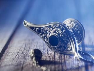 silver aladdin's lamp on a dark wooden background