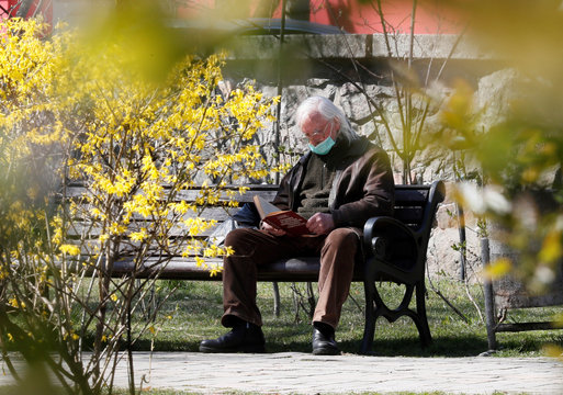 A man wearing a protective mask reads a book as he rests in a park in central Kiev