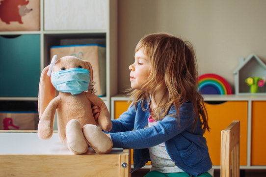Toddler girl playing with rabbit soft toy in the medicine mask