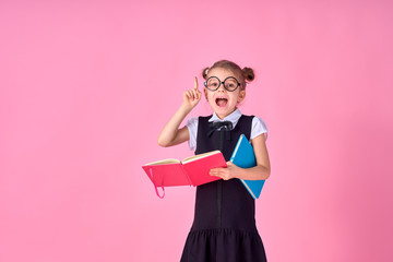 A picture of a schoolgirl with textbook emotionally guessing pointing at something over isolate pink background.