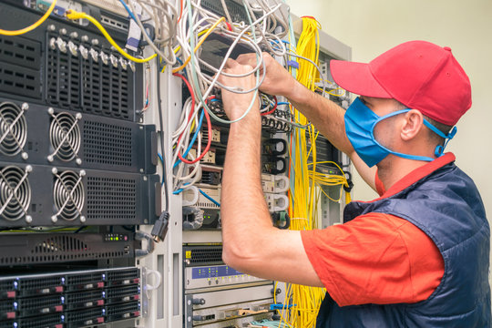 A technician in a medical mask switches wires in the server room. A man in a red cap works in a datacenter. A technical employee maintains computer equipment