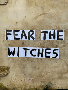 """Protest poster against domestic violence and femicide stuck on a wall saying """"fear the witches"""""""
