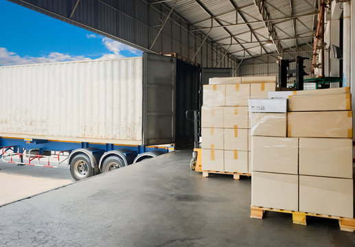 Interior of distribution warehouse, stack of package boxes, large pallet shipment goods, truck dock warehouse loading cargo , road freight industry delivery, shipping ,logistics and transport