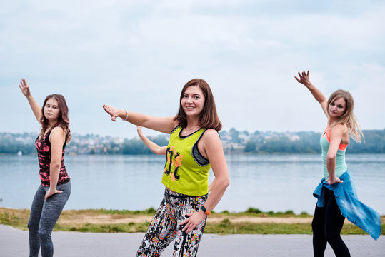 A group of young women, wearing colorful sports outfits, doing zumba exercises outside by city lake. Dancing training to loose weight in summer. Healthy lifestyle concept. Female sport leisure.