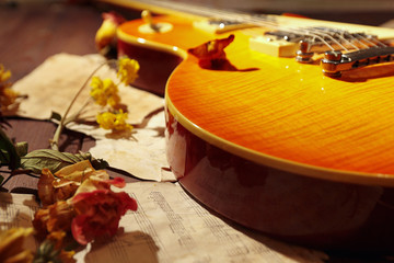 Vintage electric blues guitar, dried flowers and old notes close up.