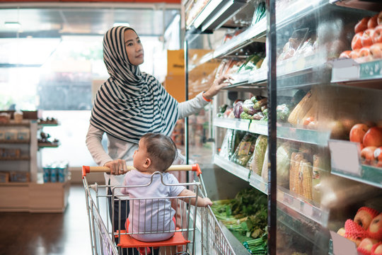 muslim asian Mother hijab and baby shopping in the supermarket. grocery store shopping