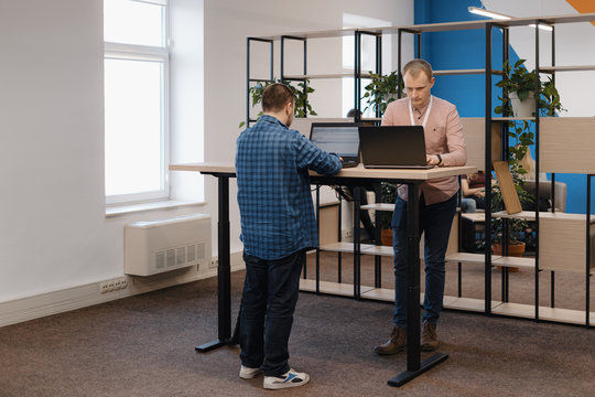 Two IT coders working on the laptop standing at the table in the office