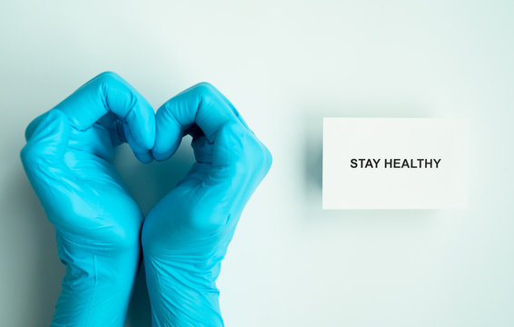 stay home and healthy to prevent covid-19 spread campaign, text on paper with heart shape hands of doctor wearing blue gloves