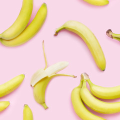 Fototapete - Bananas on a pink background, top view. Seamless pattern, food background.
