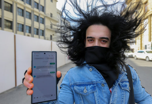 A man shows his mobile phone with permission to leave home received in a text message, in Baku