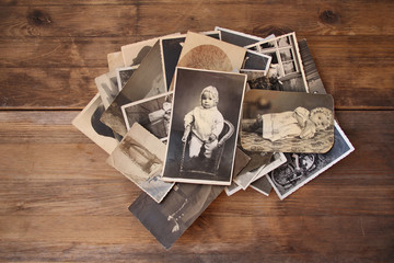old vintage monochrome photographs in sepia color are scattered on a wooden table, the concept of...
