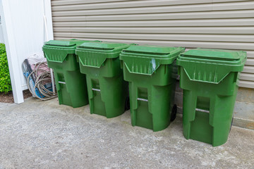 Four Plastic Trash Cans With Other Garbage