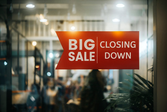 Big sale Closing Down  sign painted on the window of a dress shop.