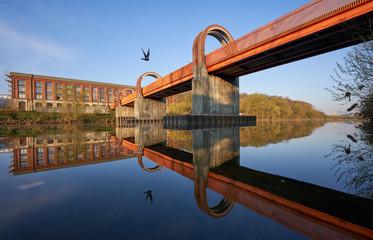 Altes Spinnerei Gebäude spiegelt sich am frühen kalten morgen im Wasser des Neckars, Taube fliegt vorbei