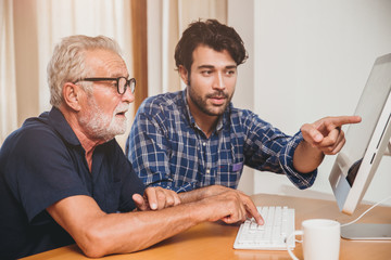 young man or son teaching his grandfather elderly dad learning to using computer at home.