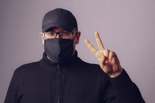 A man in a black mask on his face and glasses against a wall, toned. The concept of the pandemic covid-19 (coronavirus infection). Emotion victory