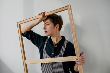 Portrait of a female painter holding a picture frame in her studio