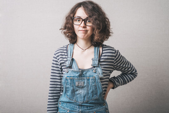 Woman in overalls dissatisfied stands with hand on hips. Gray background.