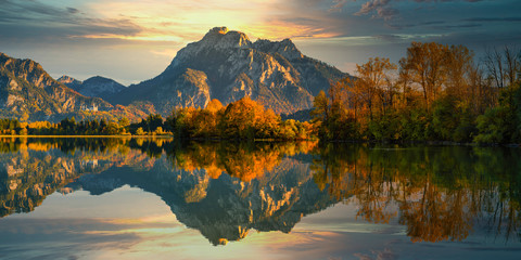 Germany, Bavaria, Hohenschwangau,?Forggensee?lake reflecting surrounding trees and hills at autumn dusk