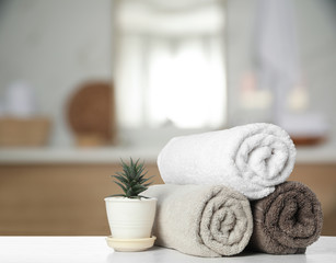 Fresh towels and houseplant on white table in bathroom. Space for text