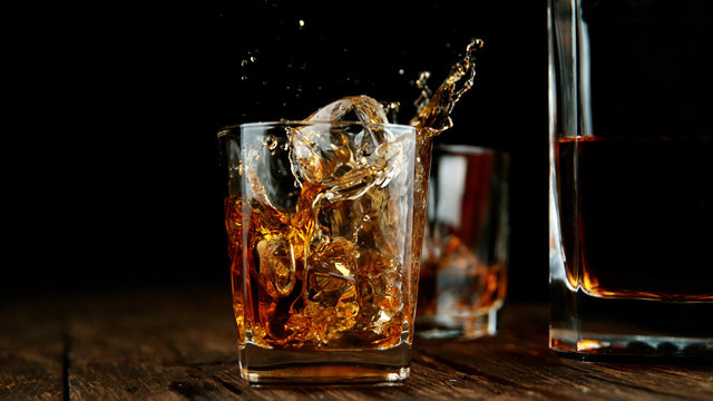 Splashing whiskey from glass with ice cubes inside