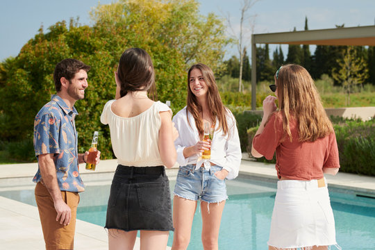 Four best friends drinking beers near swimming pool.