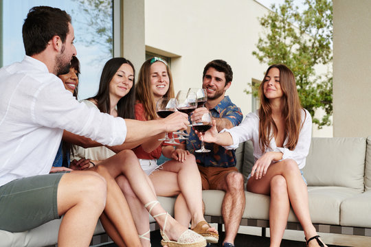Six friends cheers shaking together by glasses wine.