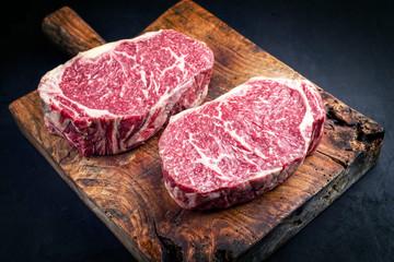 2 rohe dry aged Wagyu Entrecote Beefsteak als closeup auf einem rustikalen Holz Schneidebrett