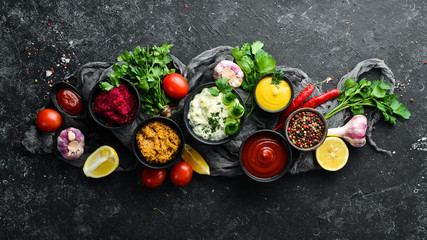 Set of colored sauces and spices on black stone background. Traditional sauces for meat and fish.