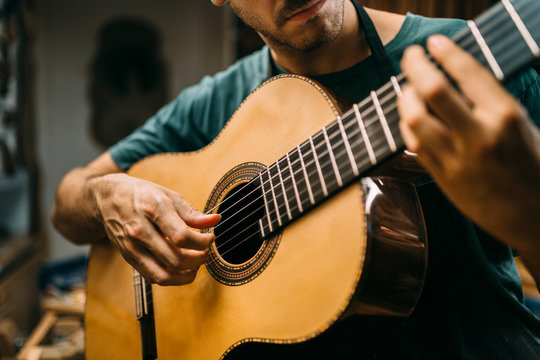 Luthier playing a spanish guitar to check the tuning and sound