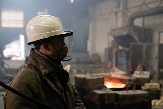 Foundry worker in helmet and mask