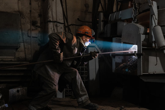 Factory worker putting bar inside furnace