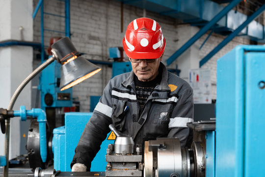 Elderly worker using lathe on factory