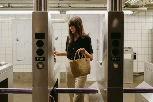 Young woman with bangs smiling walking through the turnstile in a subway stop