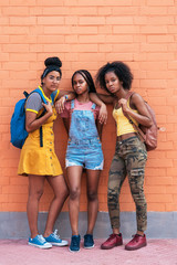 Portrait of three african american girls posing together. Looking at camera doing challenging look.