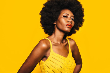 Beautiful Afro Woman posing over yellow background