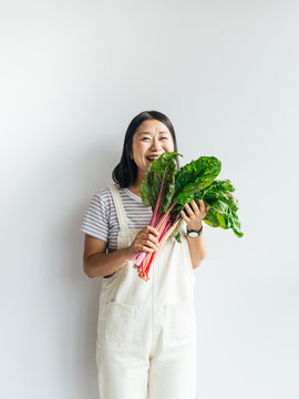 Portrait of happy female holding fresh vegetables