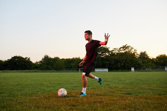 Footballer doing tricks on the pitch.