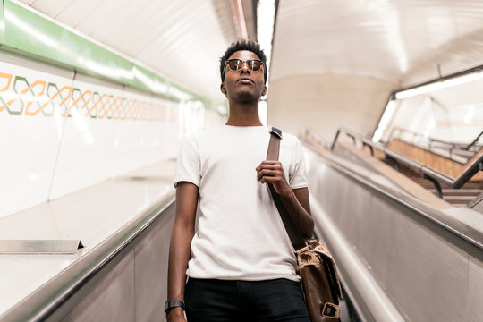 Portrait of young man moving down on escalator