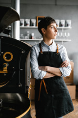 Young woman leaning on coffee machine