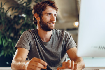 Bearded man freelancer using computer in a modern coworking place. Freelance business concept Papier Peint