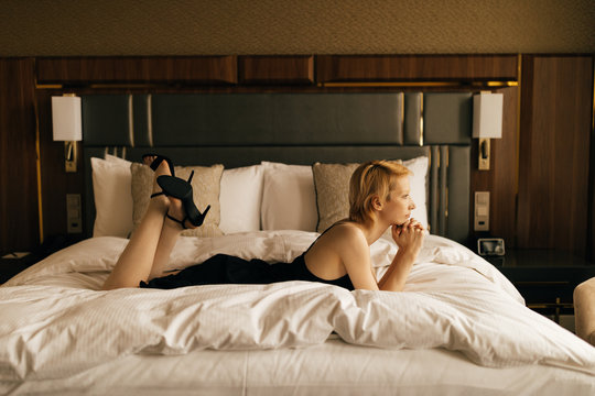 Thoughtful woman relaxing on bed at home