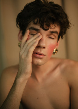 Portrait of a skinny queer guy with curly hair and golden earrings blushes and covers his face with a palm.