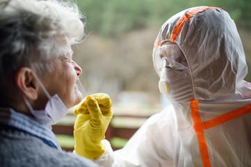 Taking corona virus test sample from nose of senior woman, quarantine concept.