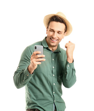 Cool young man with mobile phone dancing against white background