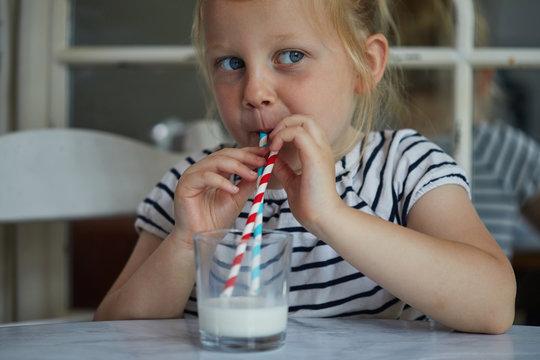 Child drinking milk through a paper straw