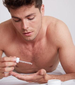 Man using oil serum skin