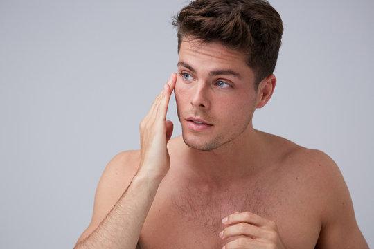 Cute man hydrating skin
