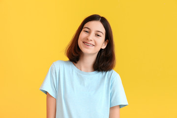 Teenage girl with dental braces on color background